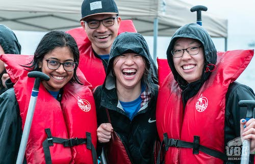 students in life jackets holding paddles