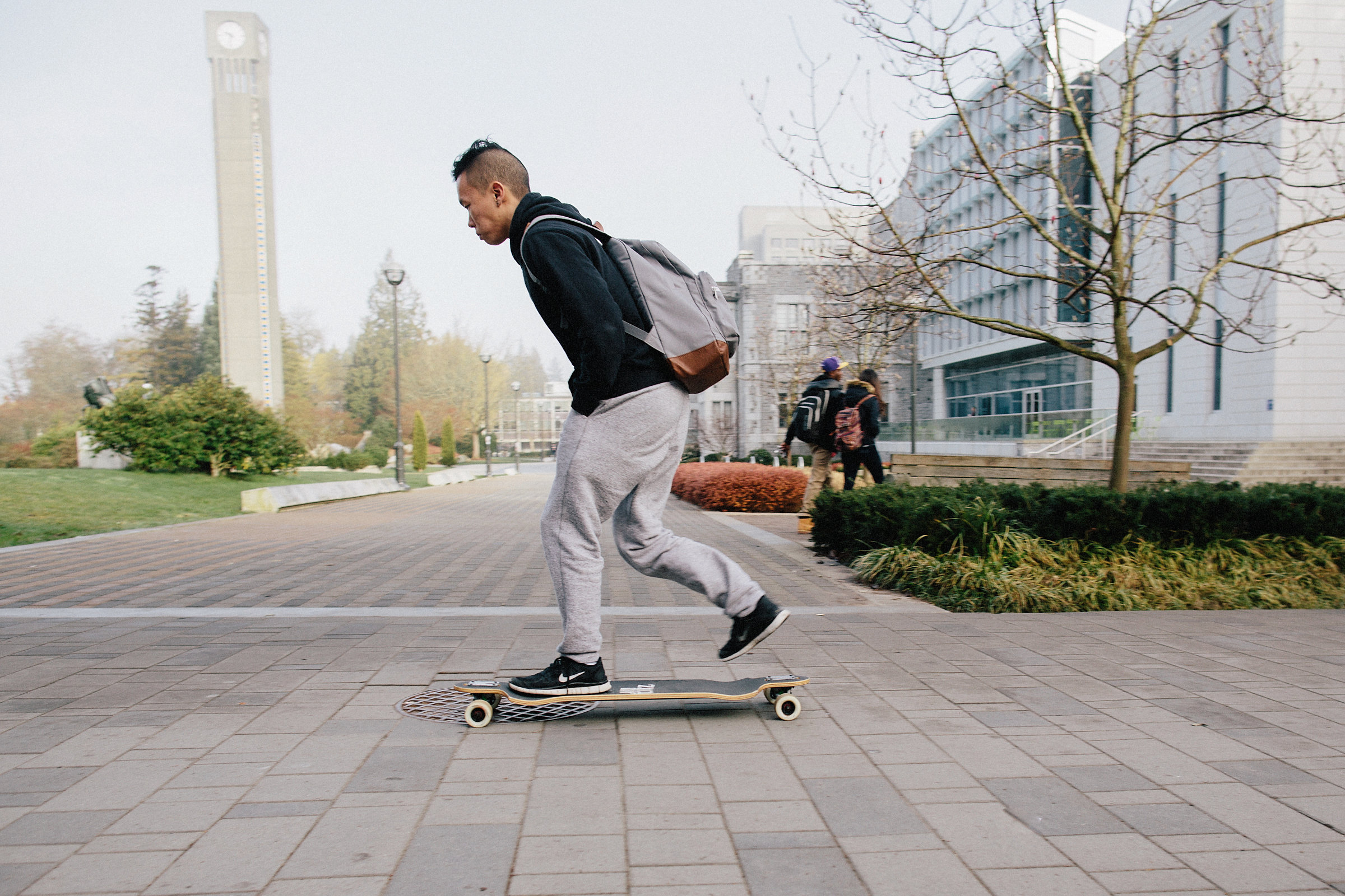 one male student long boarding on campus