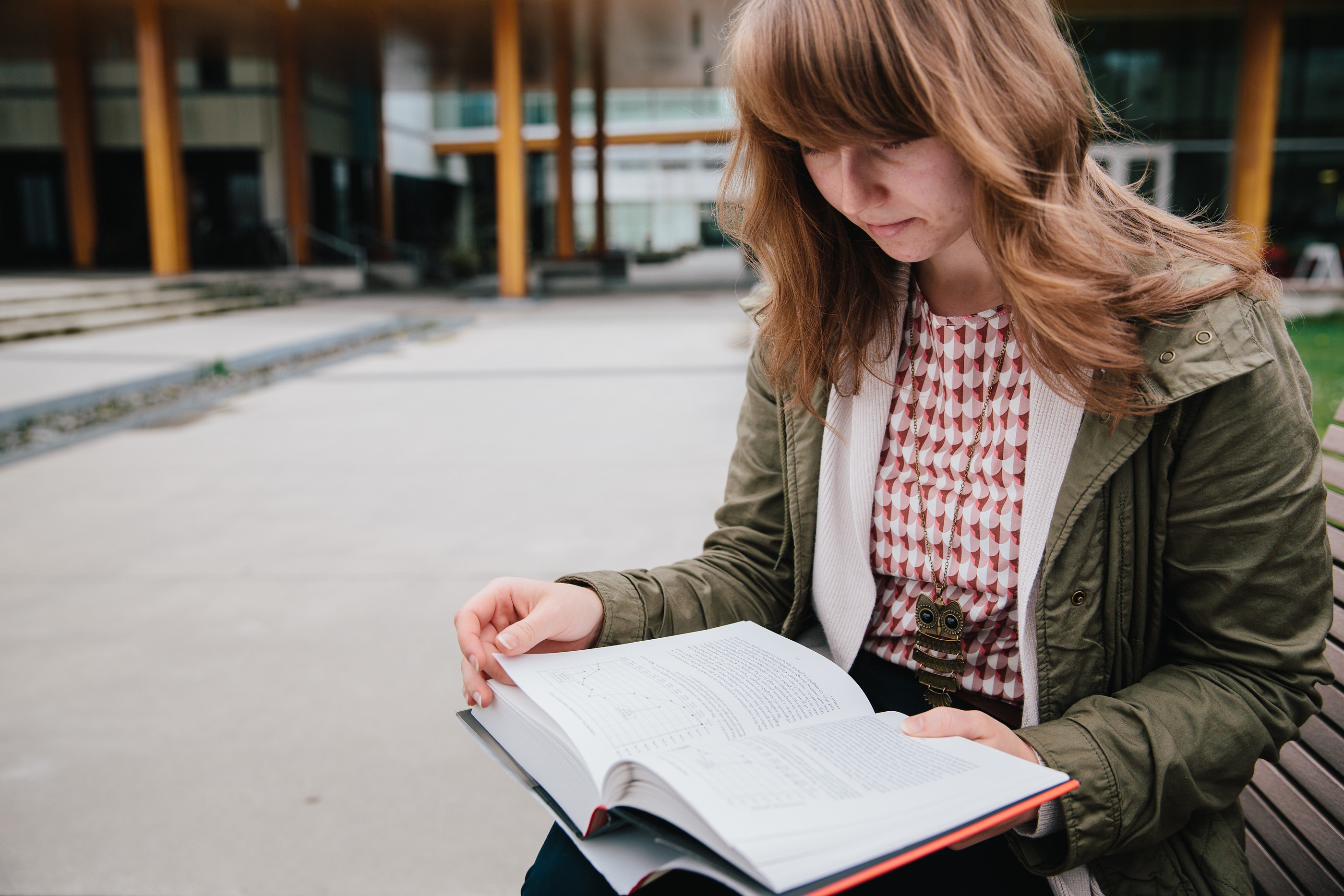 female student reading outdoors