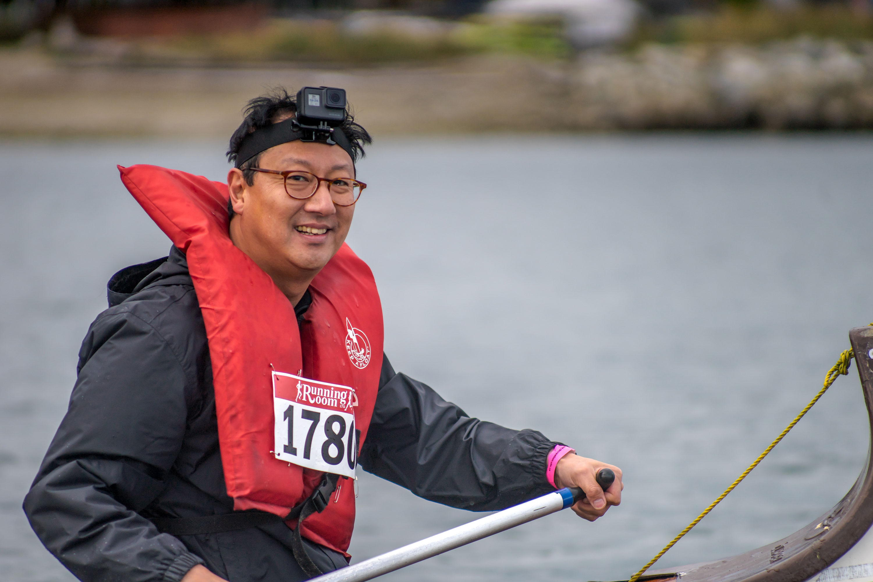 President Santa Ono paddling in a canoe at Day of the Longboat.