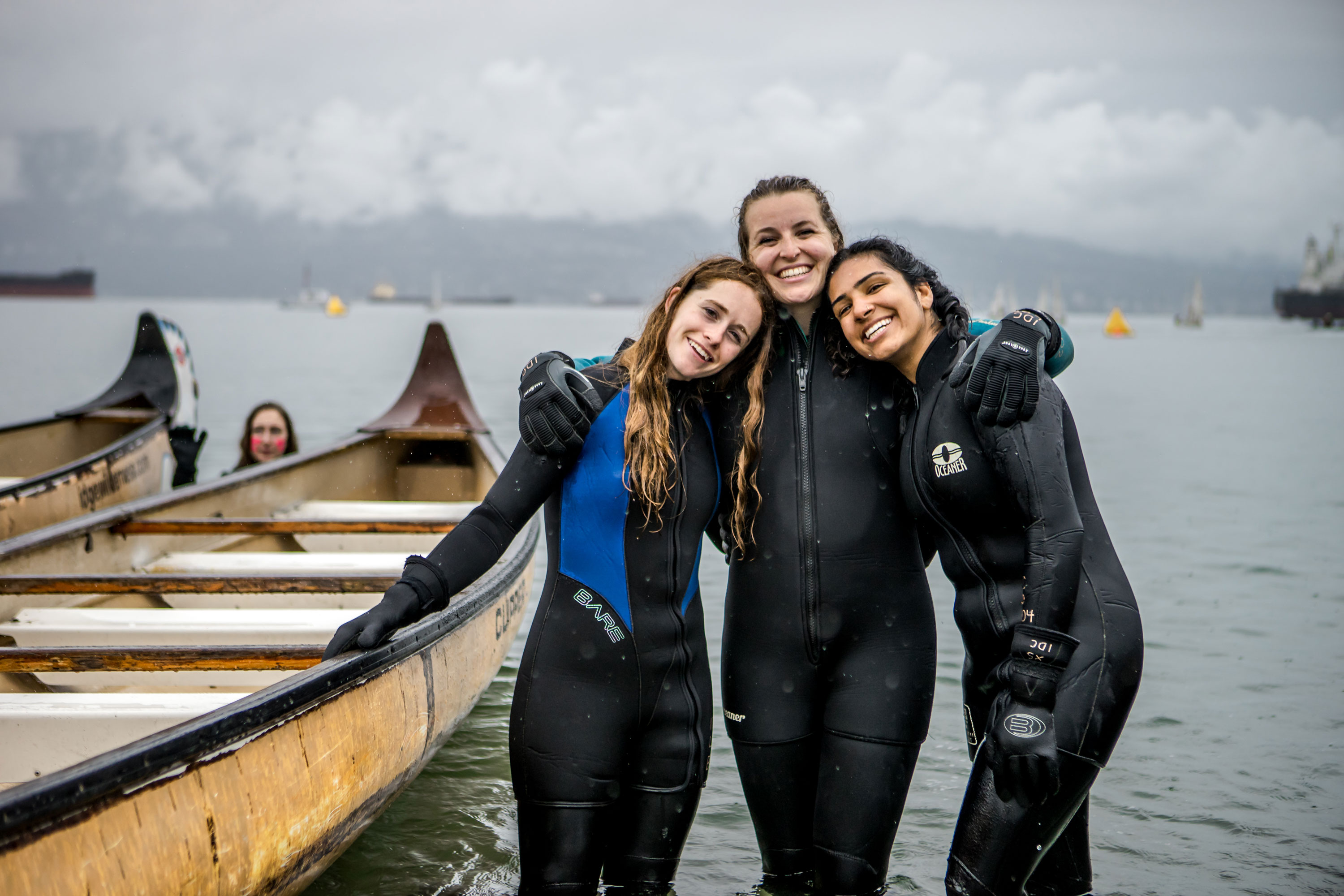 Three participants smiling while standing in water at Day of the Longboat.