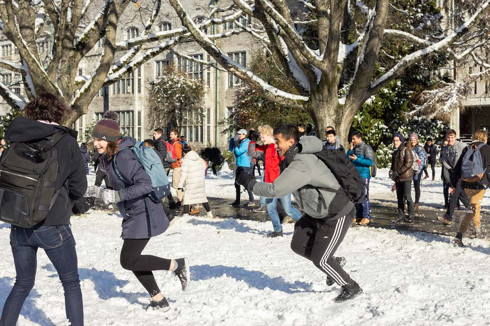 students chasing each other with snowballs