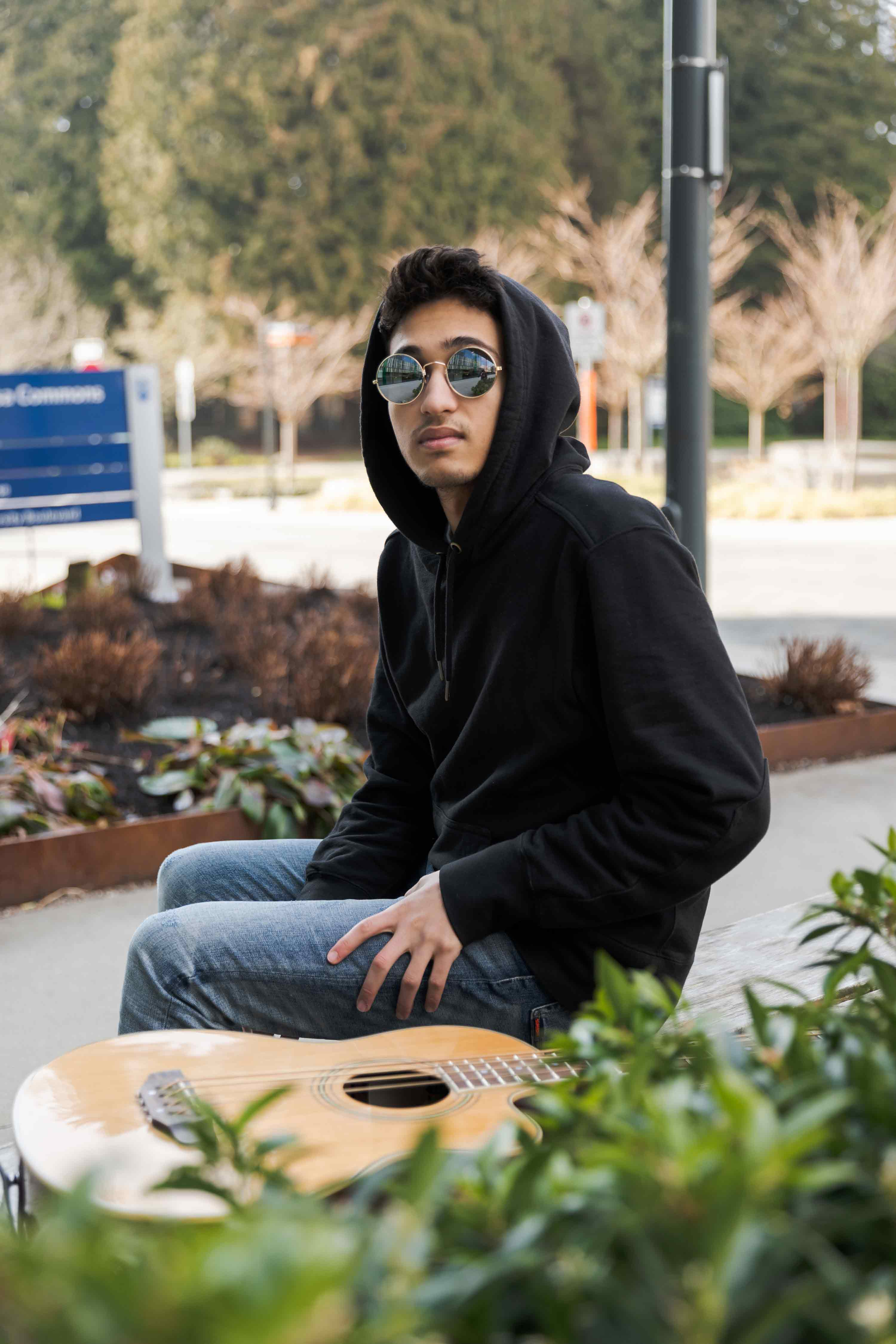 Adel sitting next to his guitar outside of Ponderosa Commons.