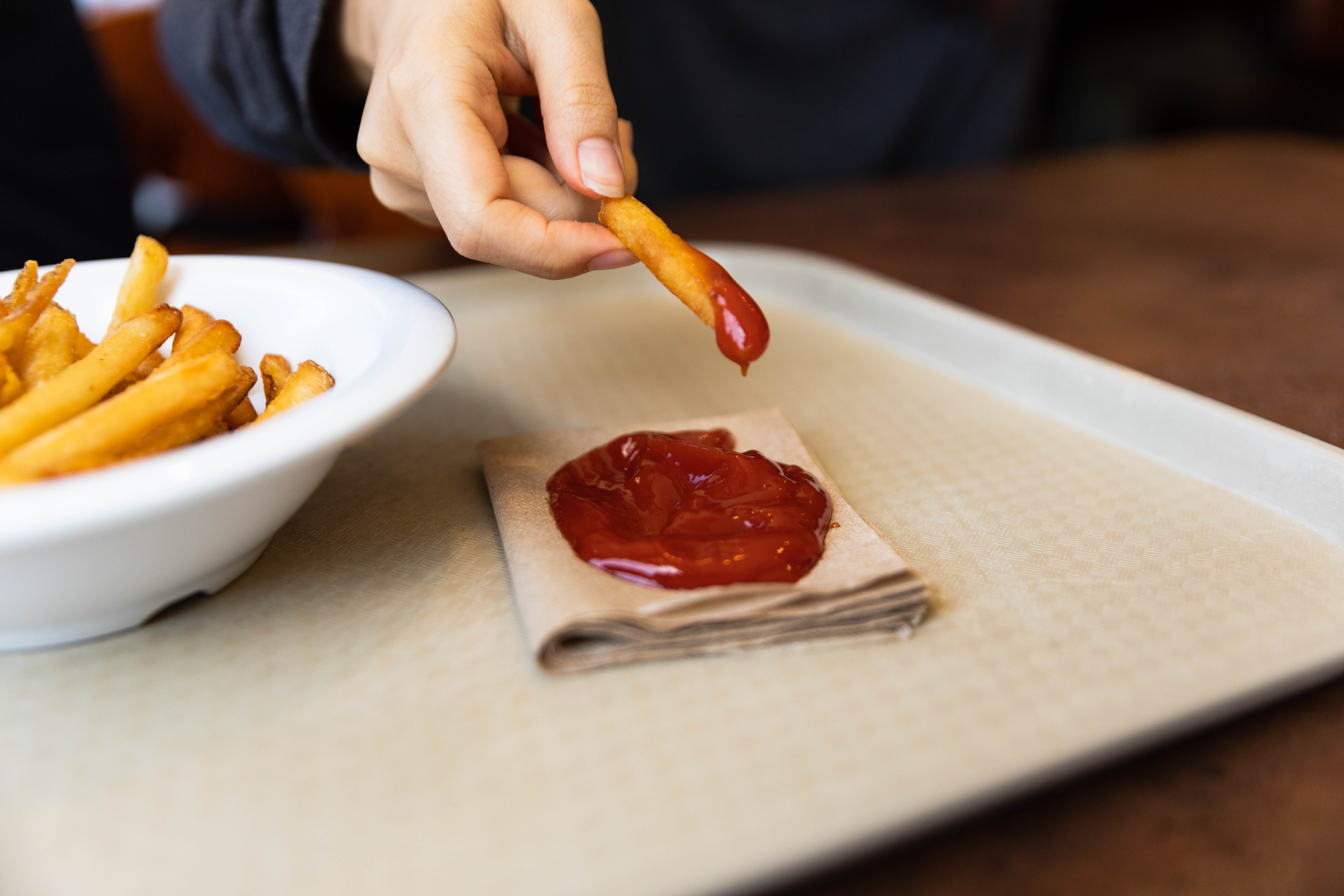 dipping a fry in ketchup