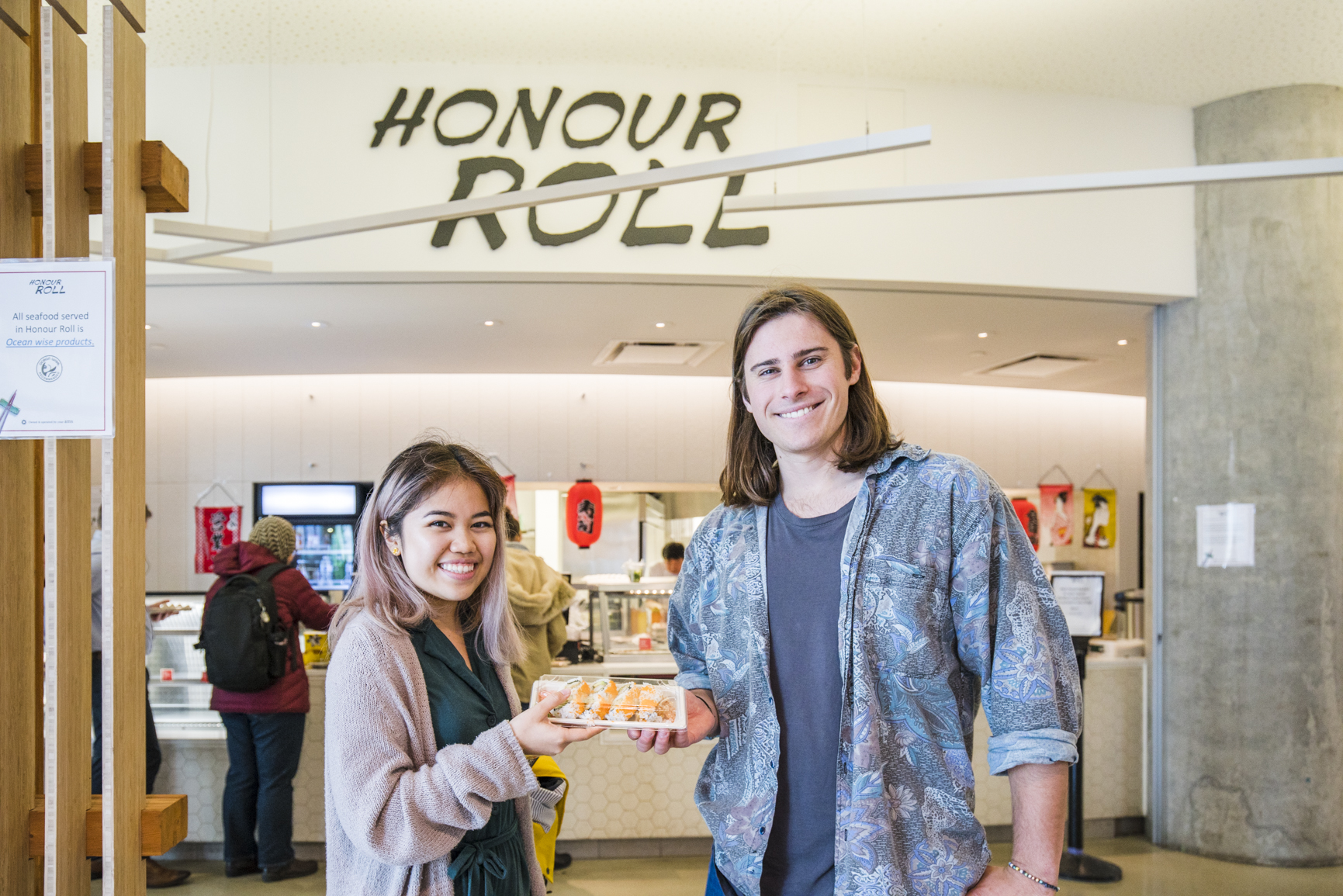 Sara and Aaron standing in front of honour roll