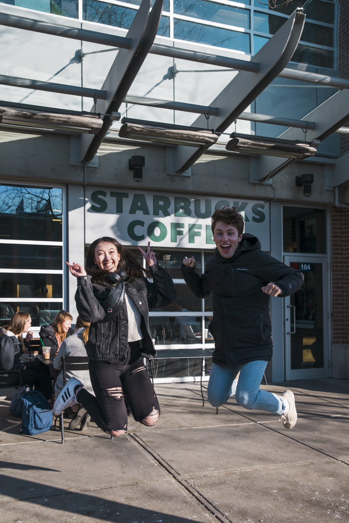 Jordan and Kana jumping in front of Starbucks