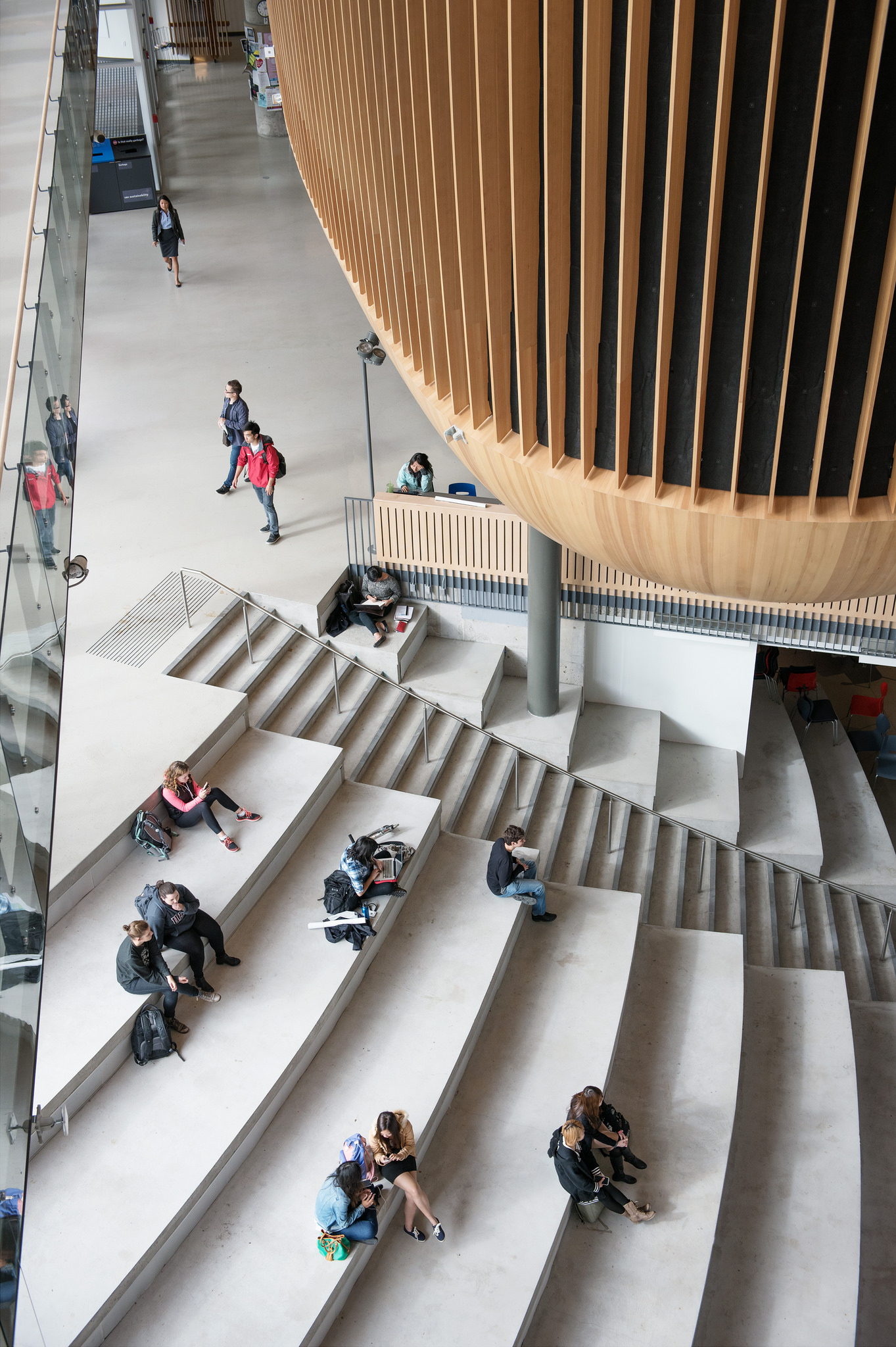 Students sitting on the steps of the Nest indoors