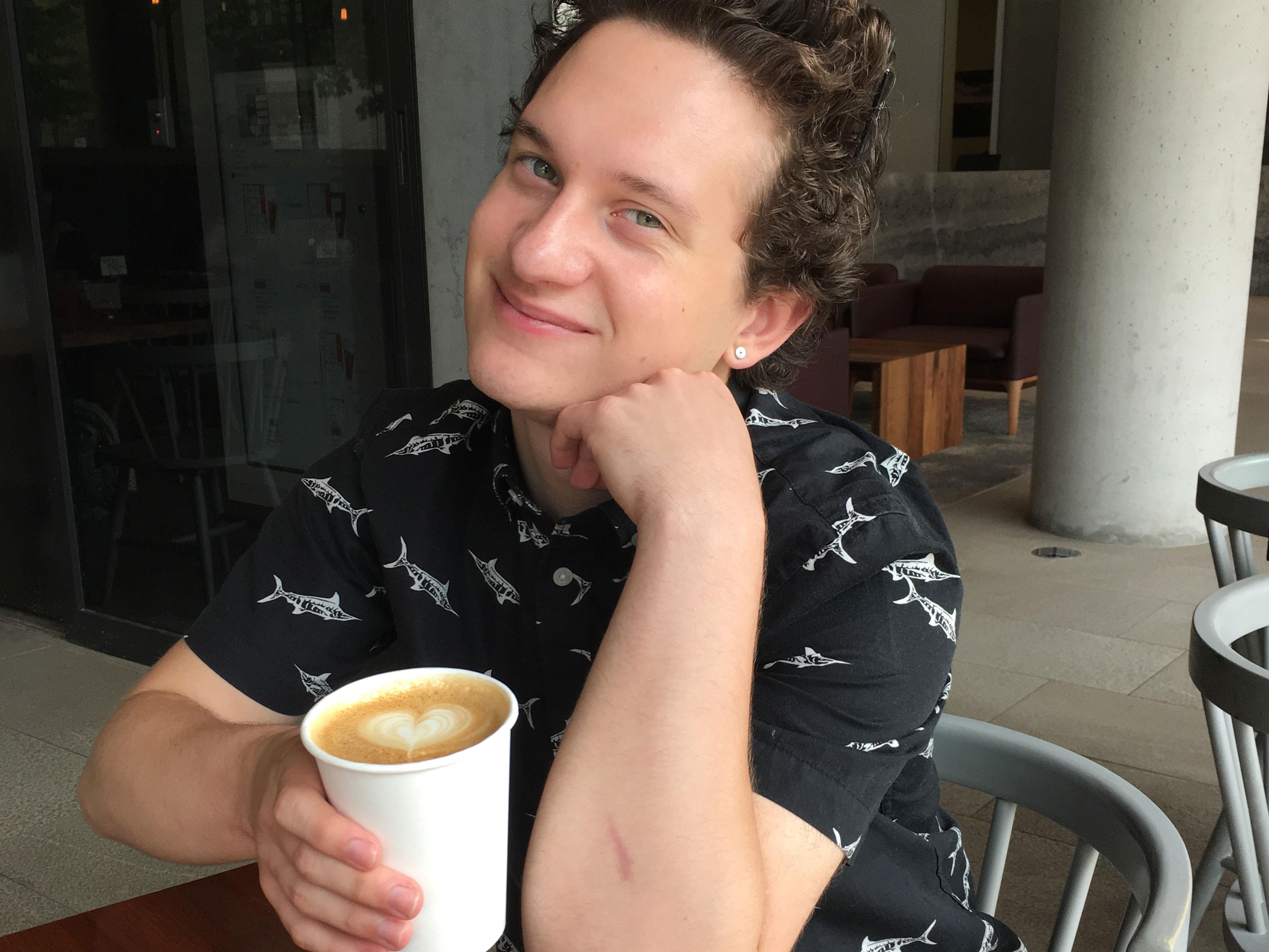 derrick holding a latte