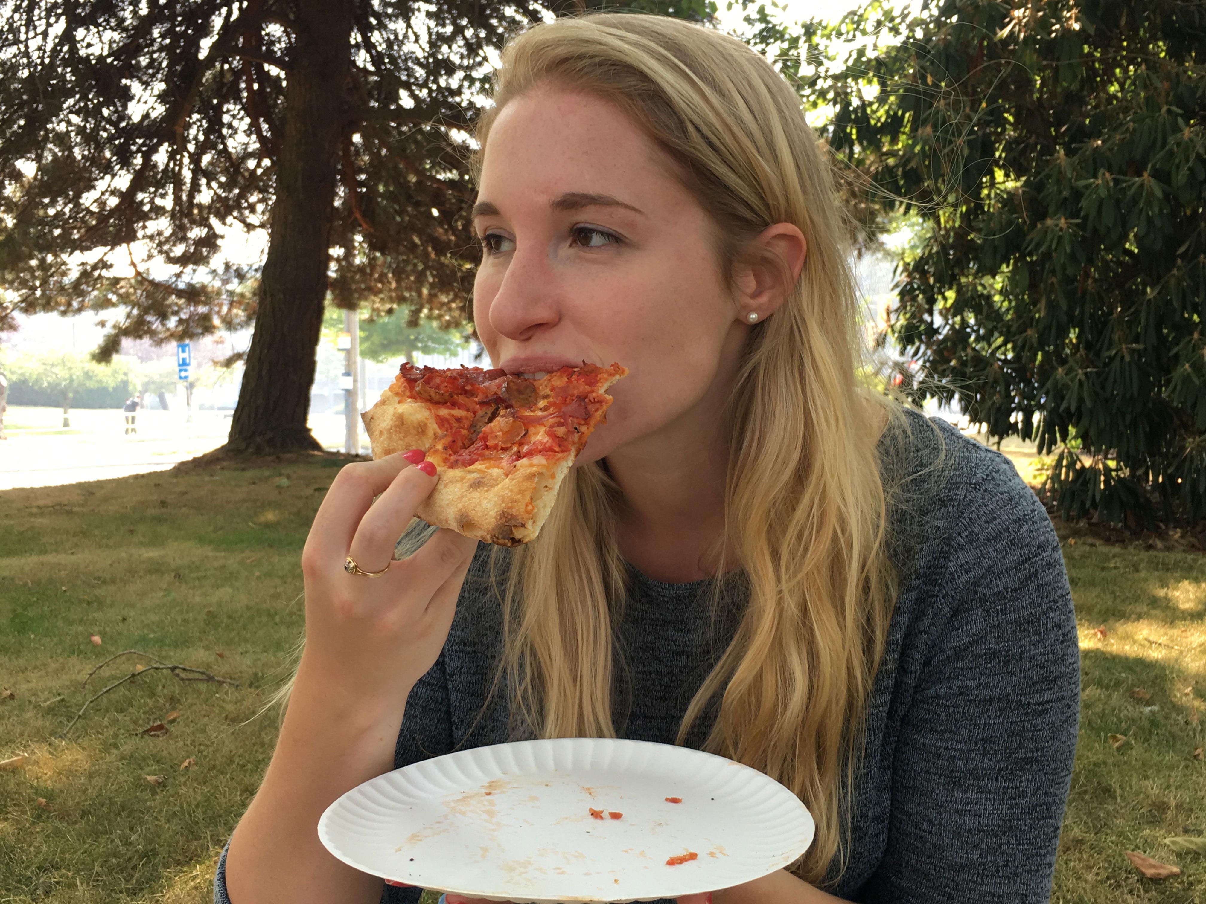 Sarah biting her pizza