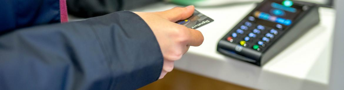 Student paying at the counter with credit card