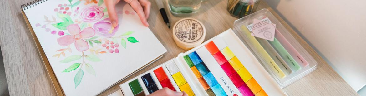 A student is painting with watercolours
