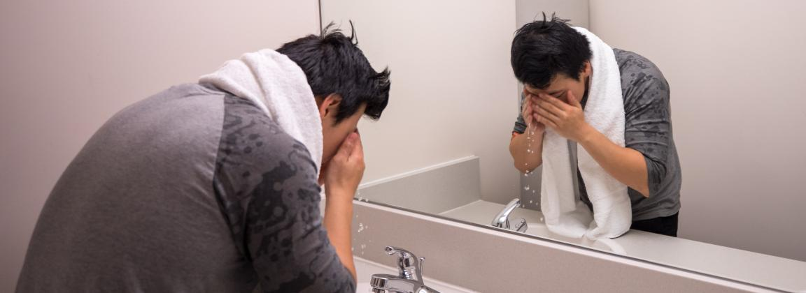 student washing his face and trying to wake up with towel around his neck