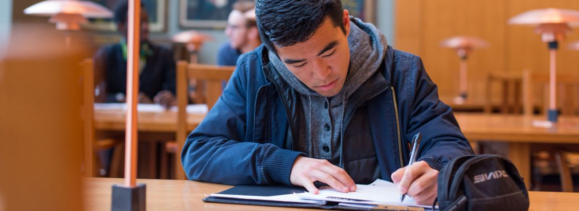 Student writing in a notebook at a UBC library