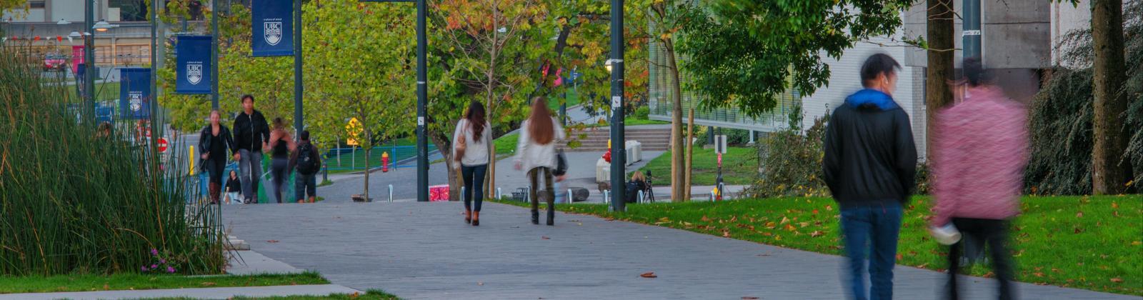 UBC students walking across UBC campus with fading light