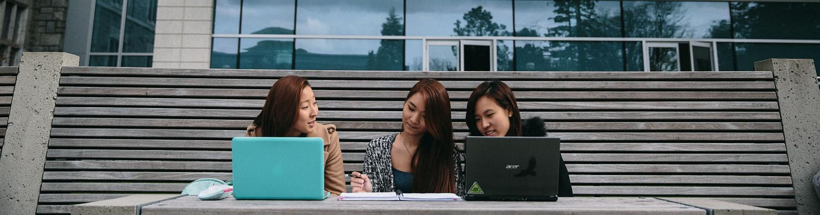Three students sitting outside at UBC with their laptops and notebooks