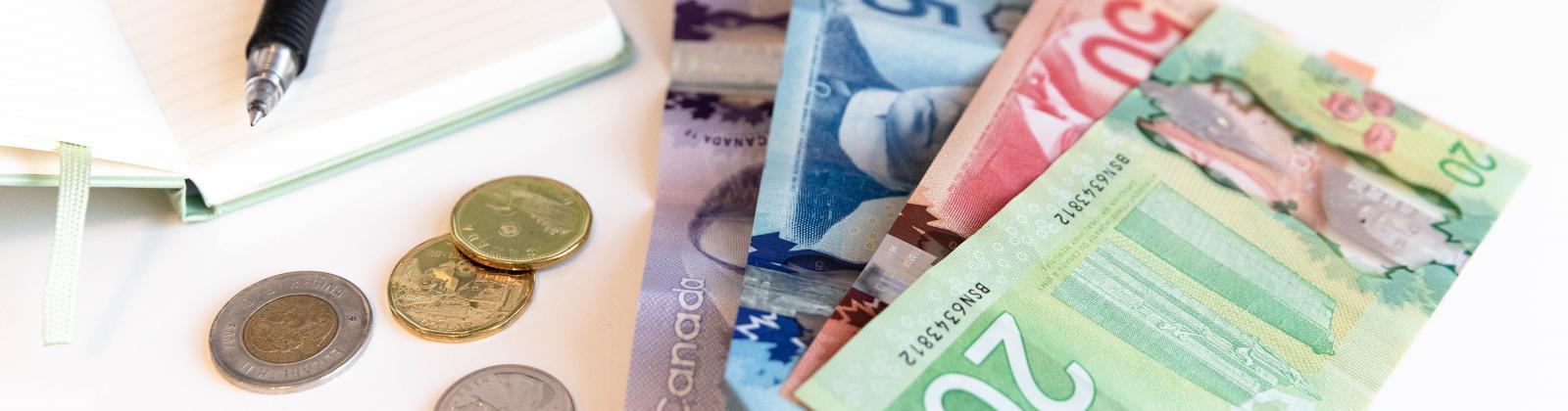 Bills and change on a desk alongside an expense notebook