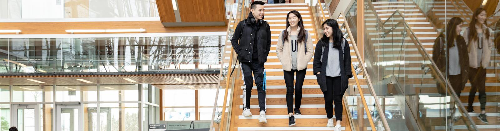 Three students walking down a flight of stairs at UBC