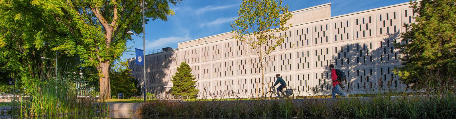 campus building with cyclists going by