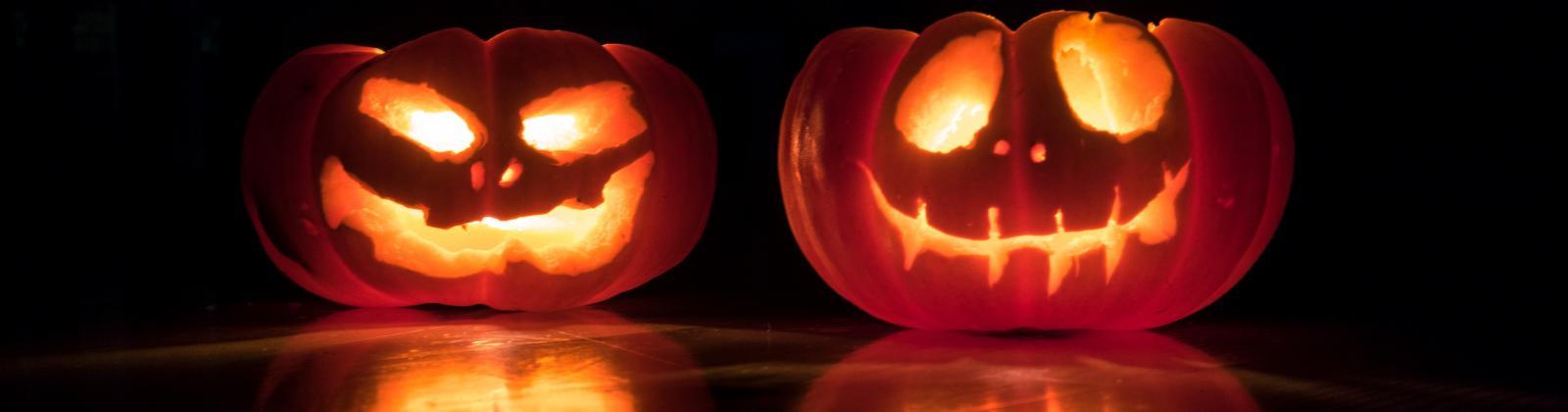Two jack-o-lanterns in a dark room