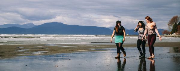 3 students walk along Wreck Beach