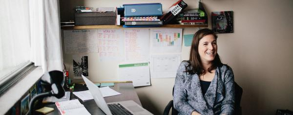 A smiling UBC student sitting at her desk