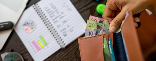 Birds-eye view shot of someone taking out cash from a wallet and of a desk with a calculator, bills, pens, and other items.