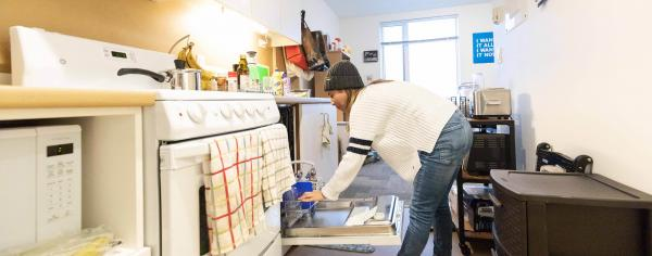 Student unloading dishwasher in her dorm