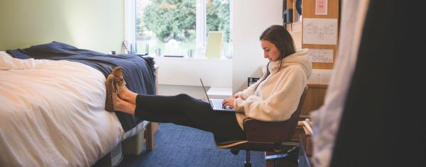 Student in a residence room looking at her laptop and relaxing