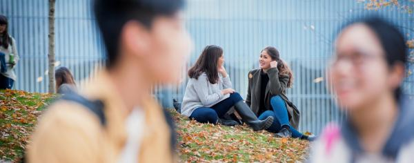 Two UBC students chatting on the grassy knoll outside the AMS Nest