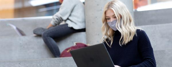 A student is sitting at the stairs, wearing a mask and studying on a laptop