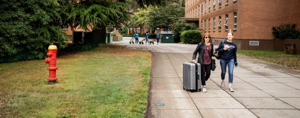 student walking with their parent and a suitcase