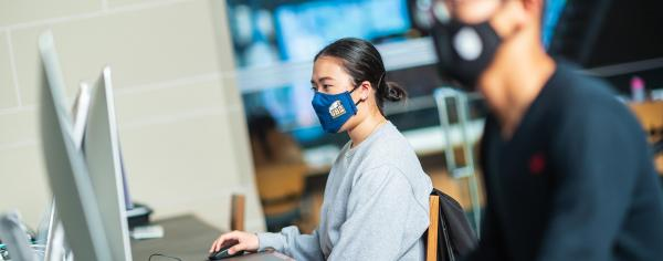 Two students wearing masks in an online class