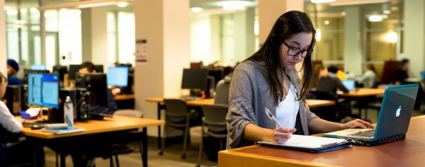 A student proofreading their work in a study space at UBC