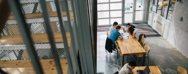 Students studying at large tables on campus