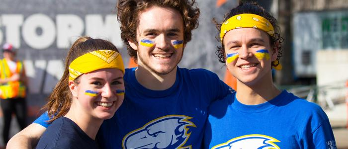 Three UBC students smiling at the camera after Storm the Wall