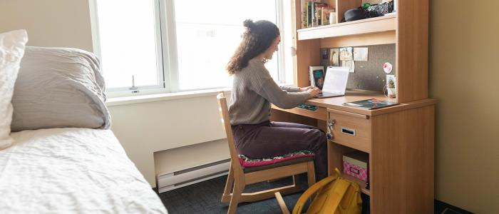 UBC student in her dormitory at her desk studying