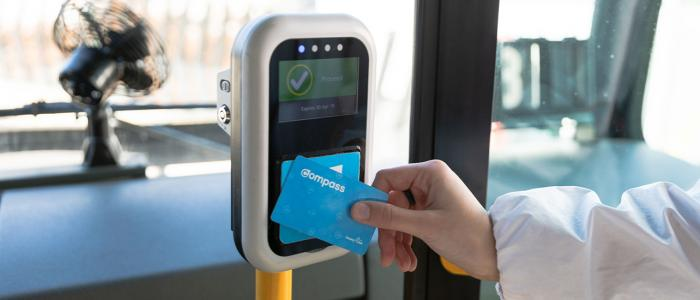 A hand tapping a Compass card against the TransLink card reader on the bus