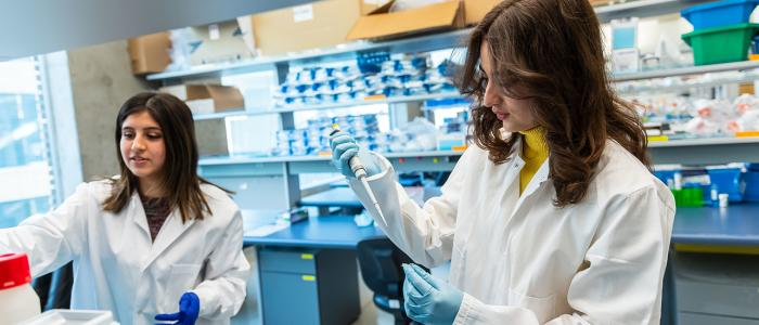 Two female students in lab coats performing a lab experiment