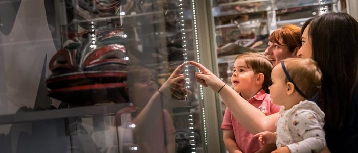 Lady with three children looking at a glass display case at a museum