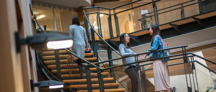 Two female UBC students on the stairs at Forestry building chatting