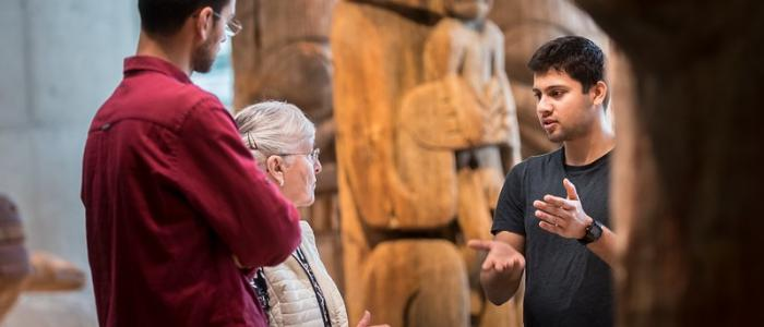 UBC student at Museum of Anthropology introducing exhibit to an elderly woman and a tall man