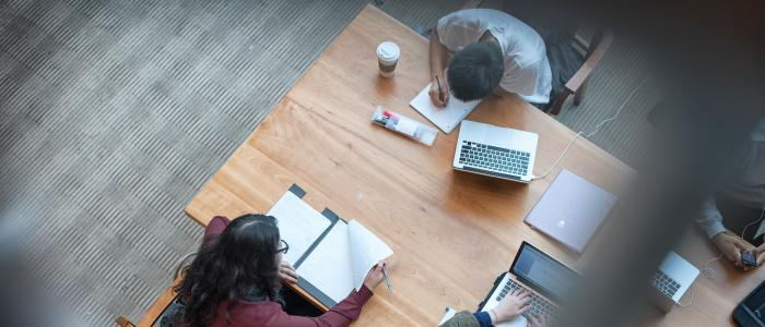 Aerial view of three UBC students studying with notebooks and laptops