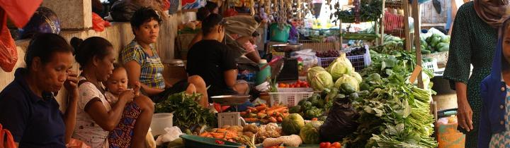 People looking on at a colourful vegetable market in Indonesia