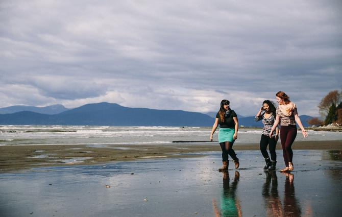 3 students walk along Wreck Beach