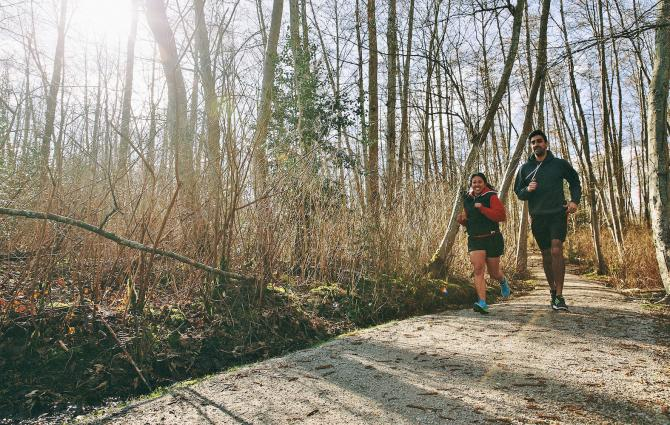 Two students running together on the Foreshore Trail by Wreck Beach