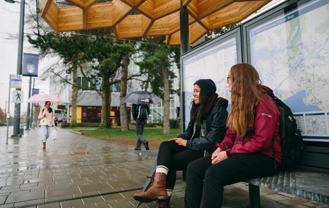 Students sitting at the bench at the bus loop