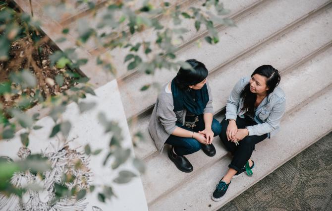 Two students sitting on the steps, talking