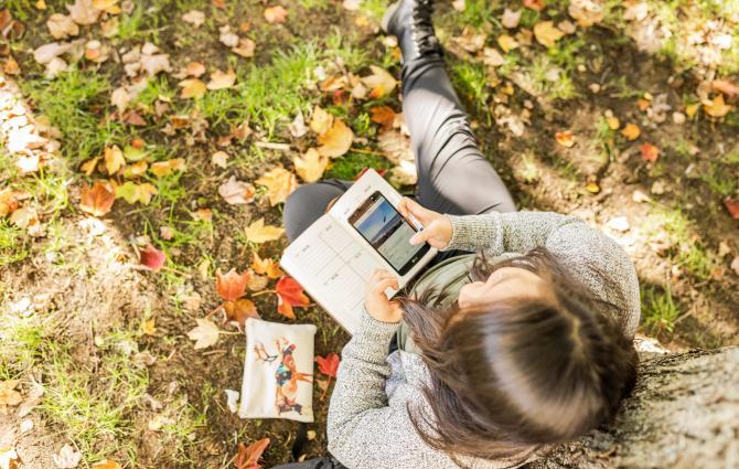 UBC student sitting outside using phone