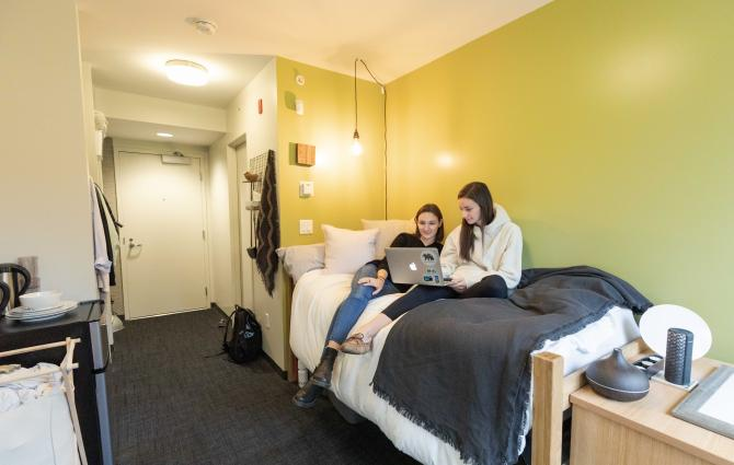 two students hanging out in a dorm room