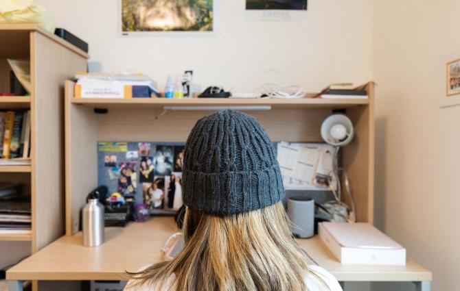 Student sitting at their desk in their dorm room